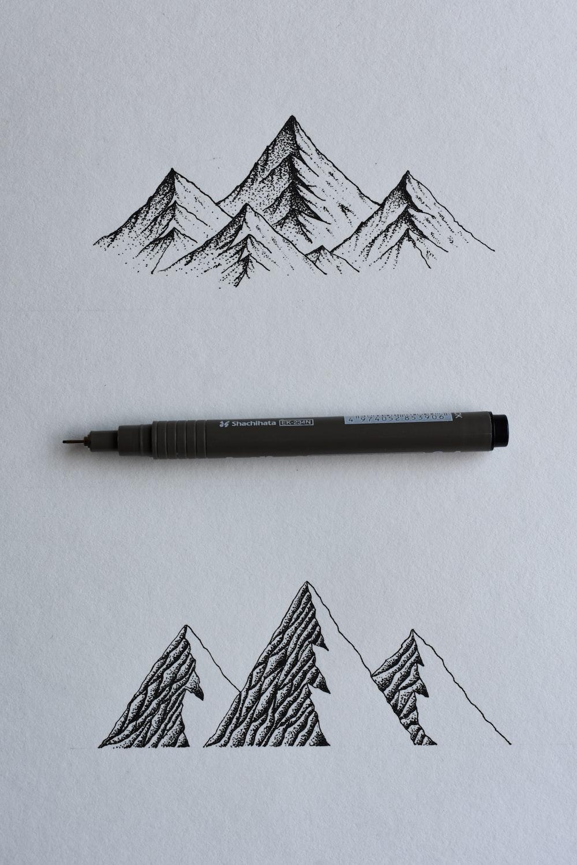 black and gray click pen on white printer paper