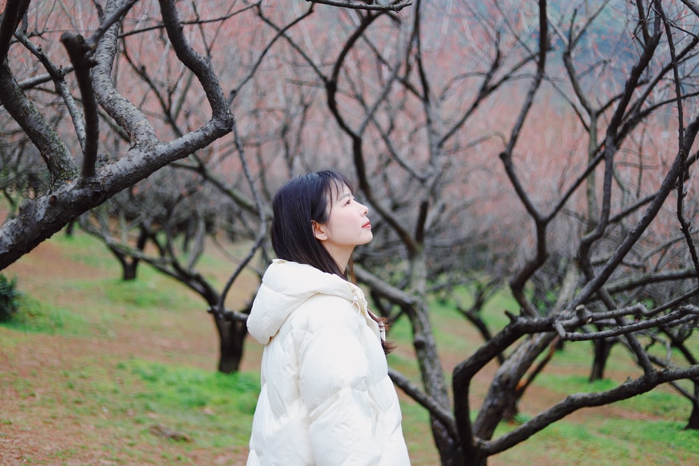 woman in white long sleeve dress standing beside brown tree during daytime