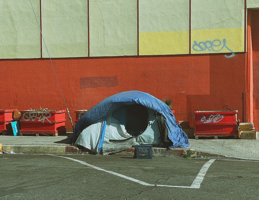 man in blue jacket lying on blue and white tent