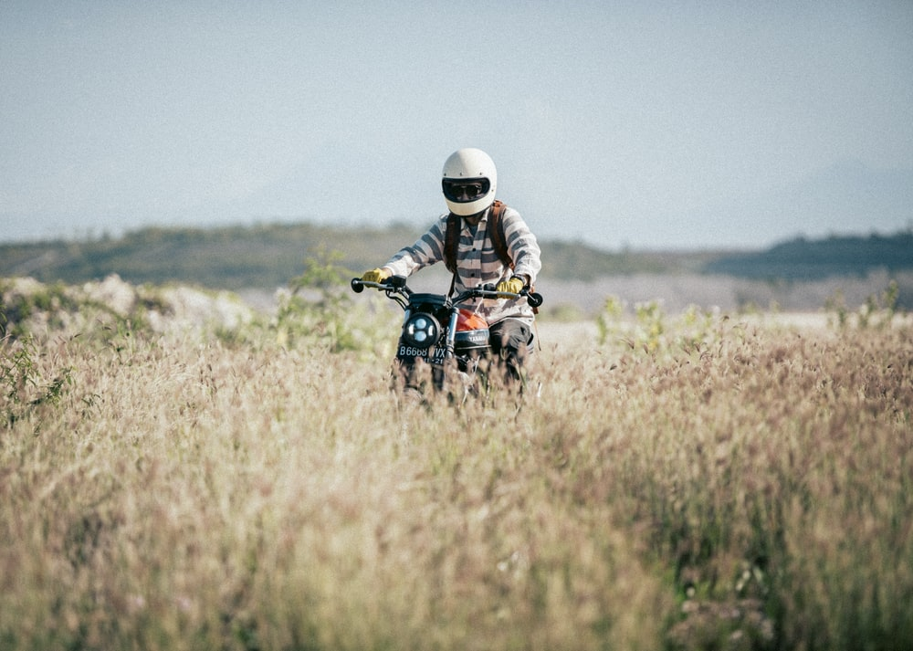 man riding motorcycle on brown grass field during daytime
