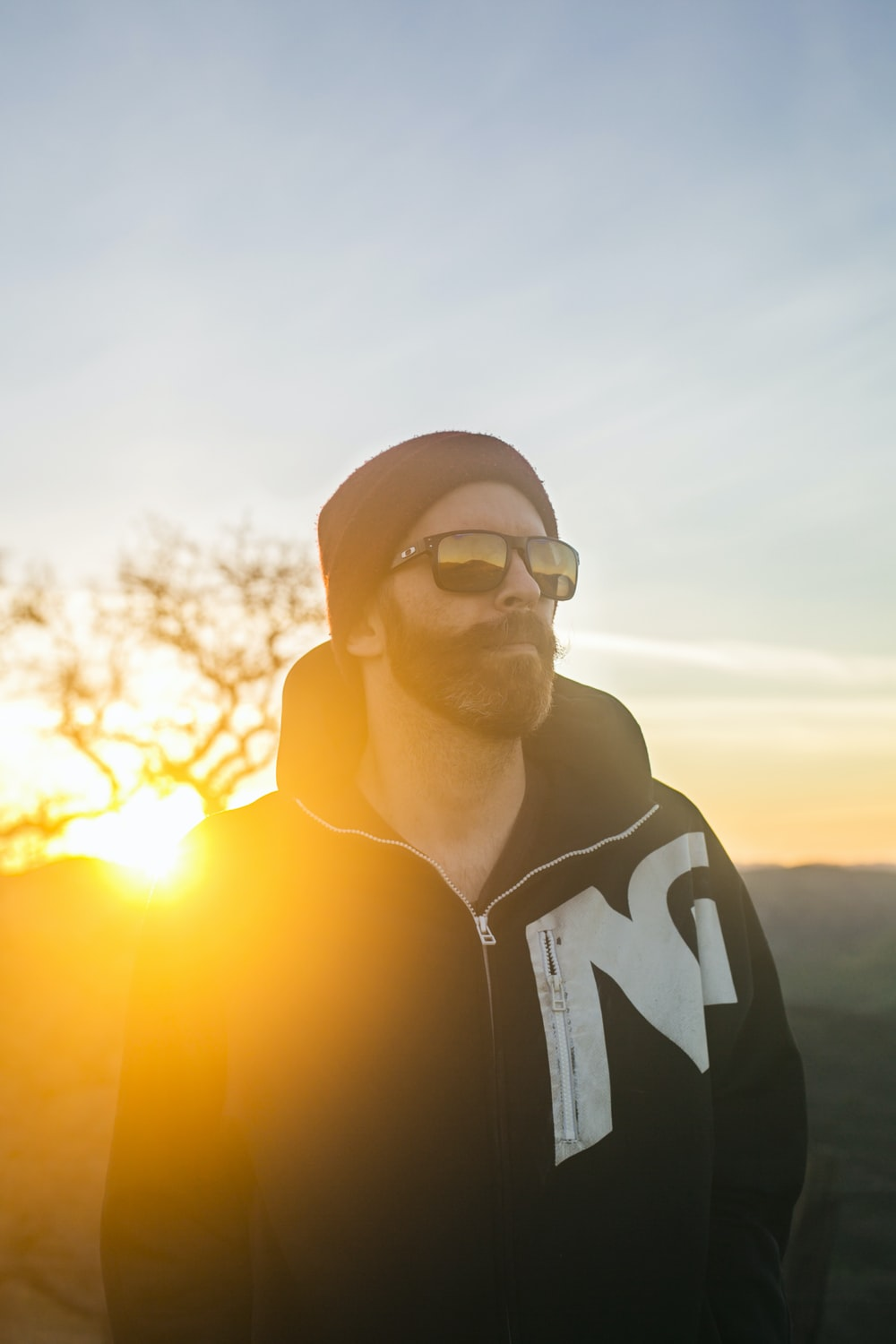 man in black and white hoodie wearing black sunglasses during sunset