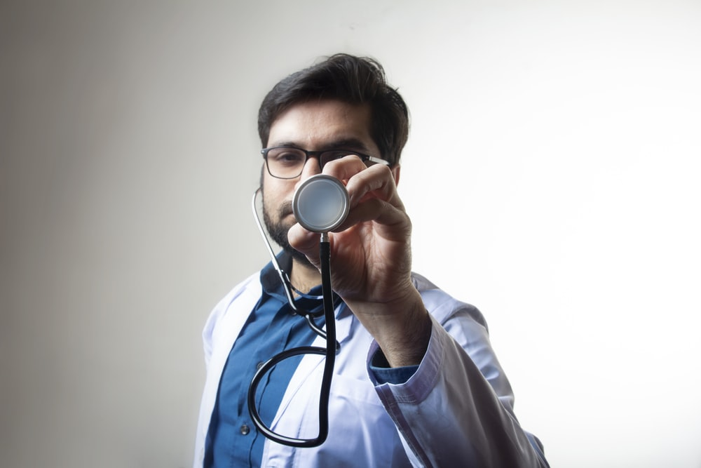 person in white shirt holding black and silver headphones