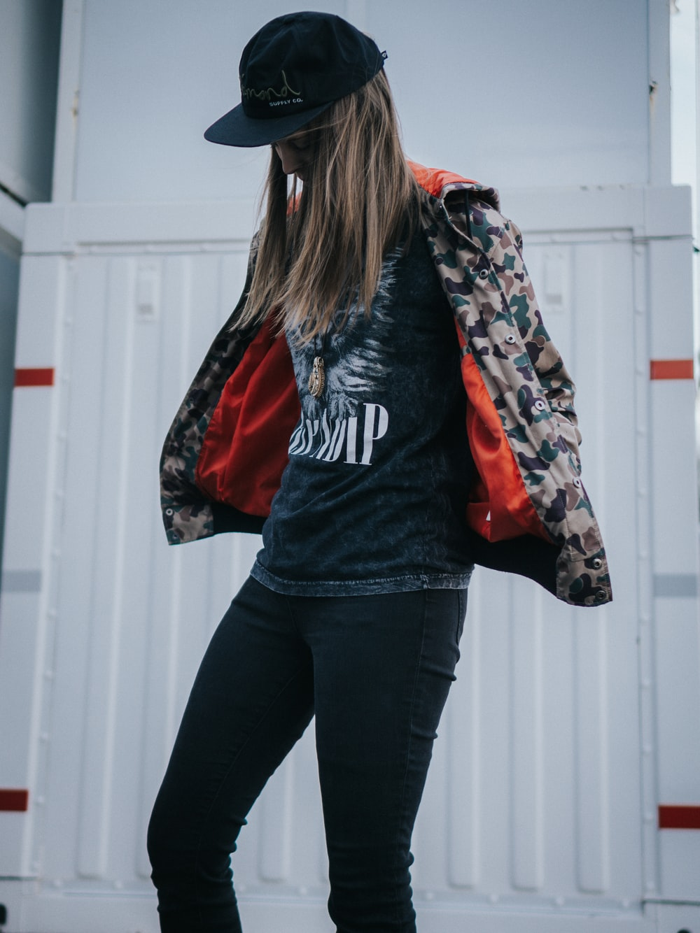 woman in black and red jacket and black pants wearing black cowboy hat
