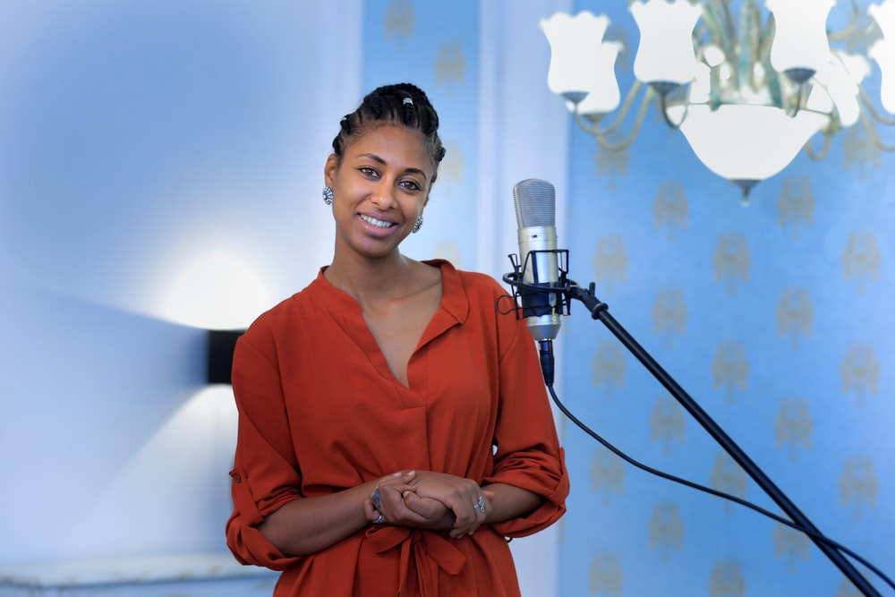 woman in orange v neck long sleeve shirt standing beside microphone