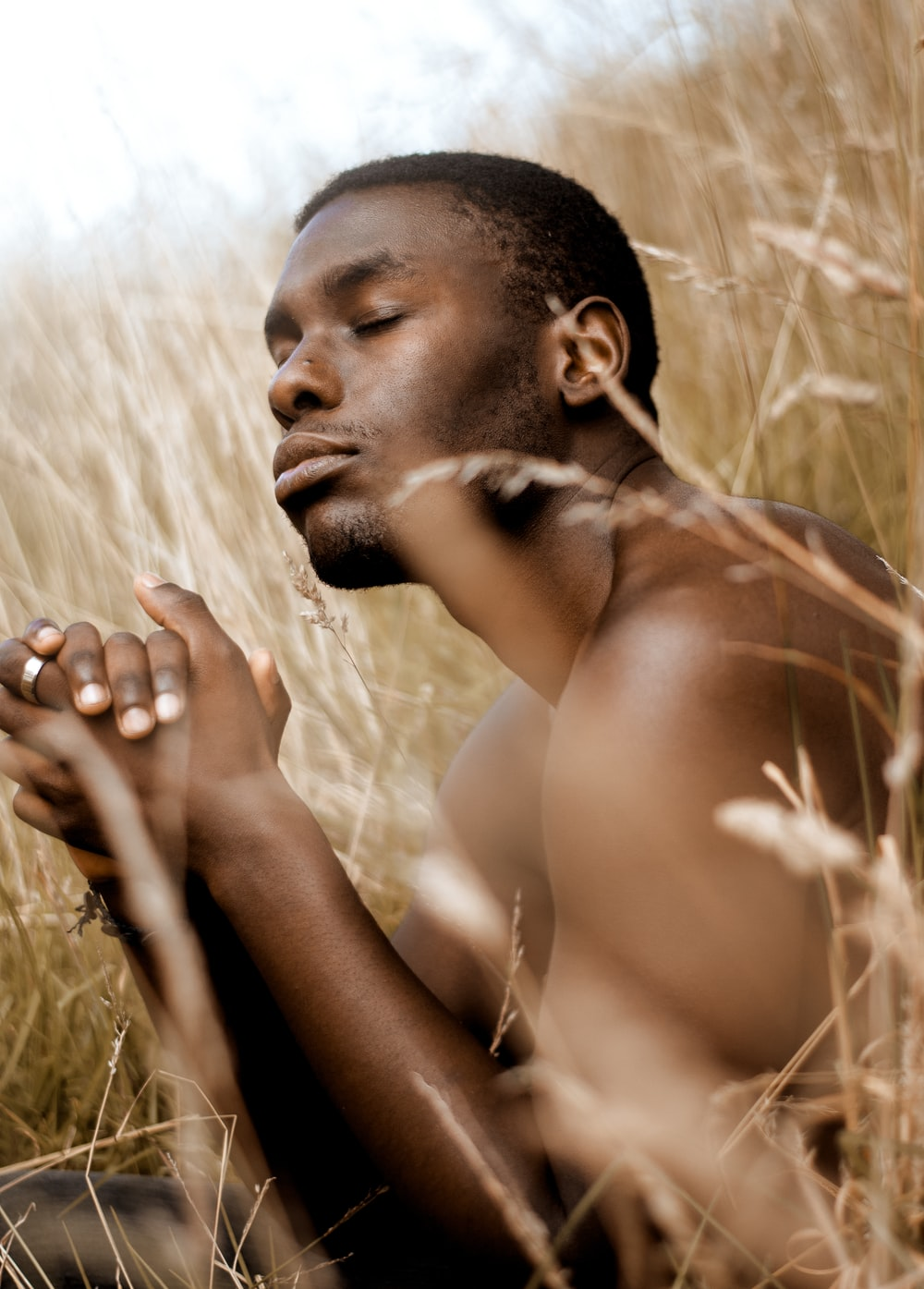 topless man sitting on brown grass field during daytime