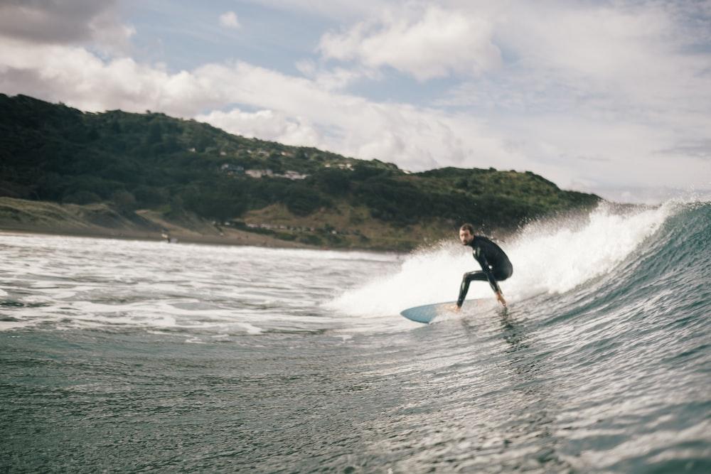 man surfing on sea during daytime