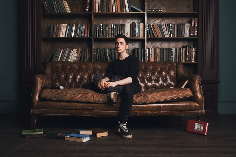 man in black long sleeve shirt sitting on brown leather couch