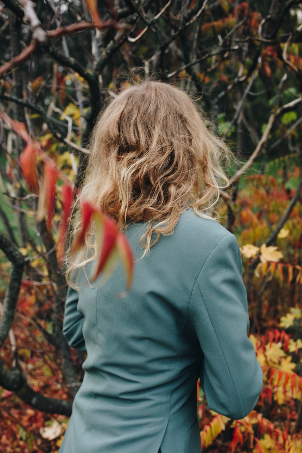 woman in gray long sleeve shirt standing near brown and green plants during daytime