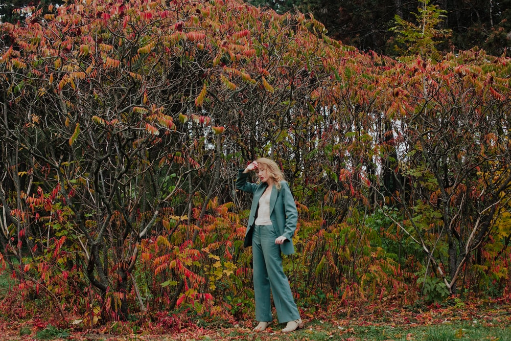 woman in blue denim jacket standing on brown dried leaves during daytime