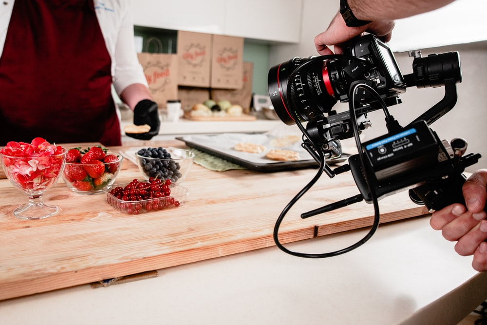 black dslr camera on brown wooden chopping board