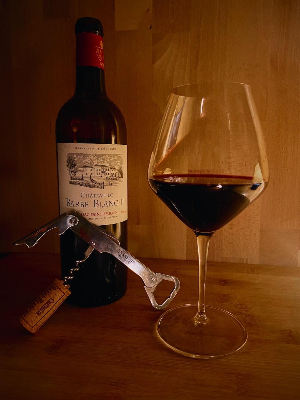 clear wine glass beside wine bottle