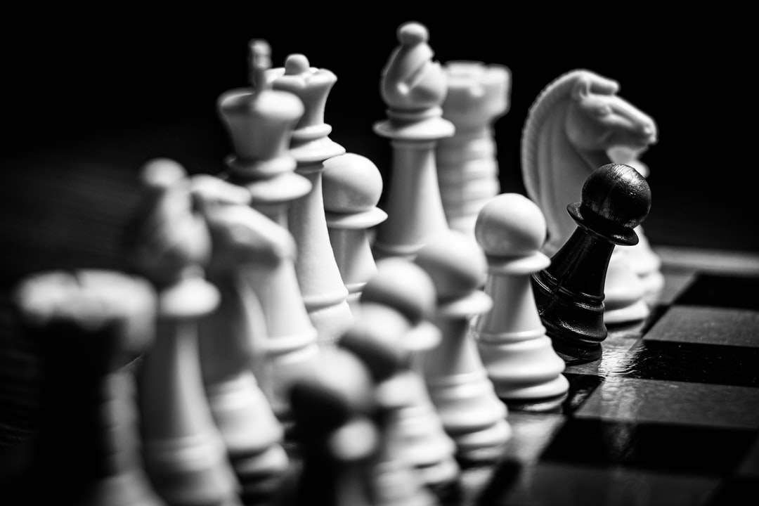 white chess piece on black surface