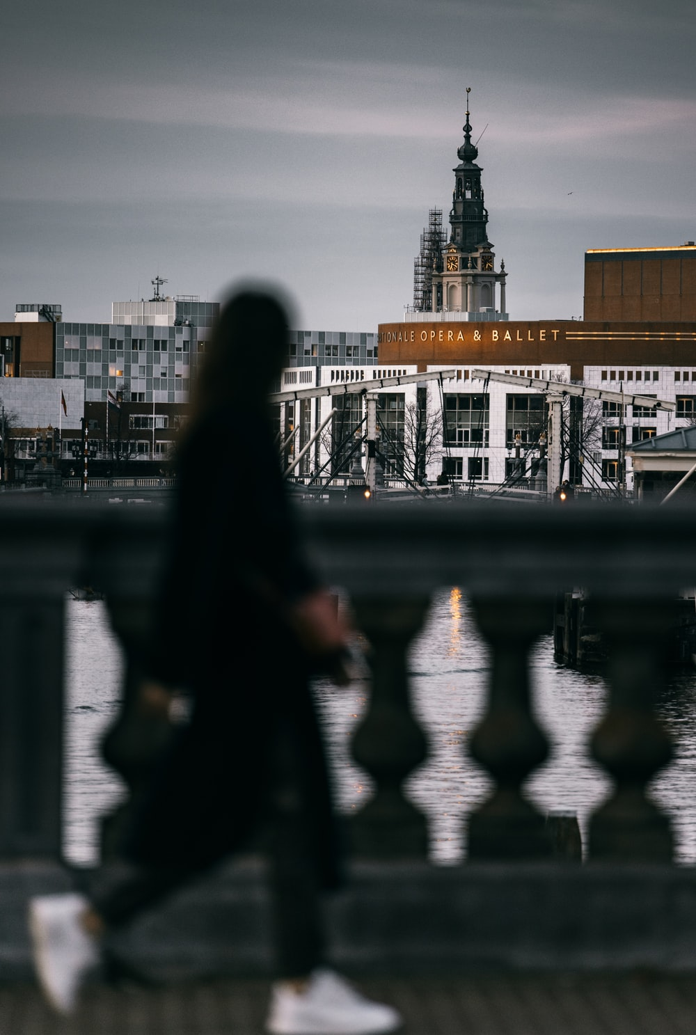 woman in black coat standing near body of water during daytime