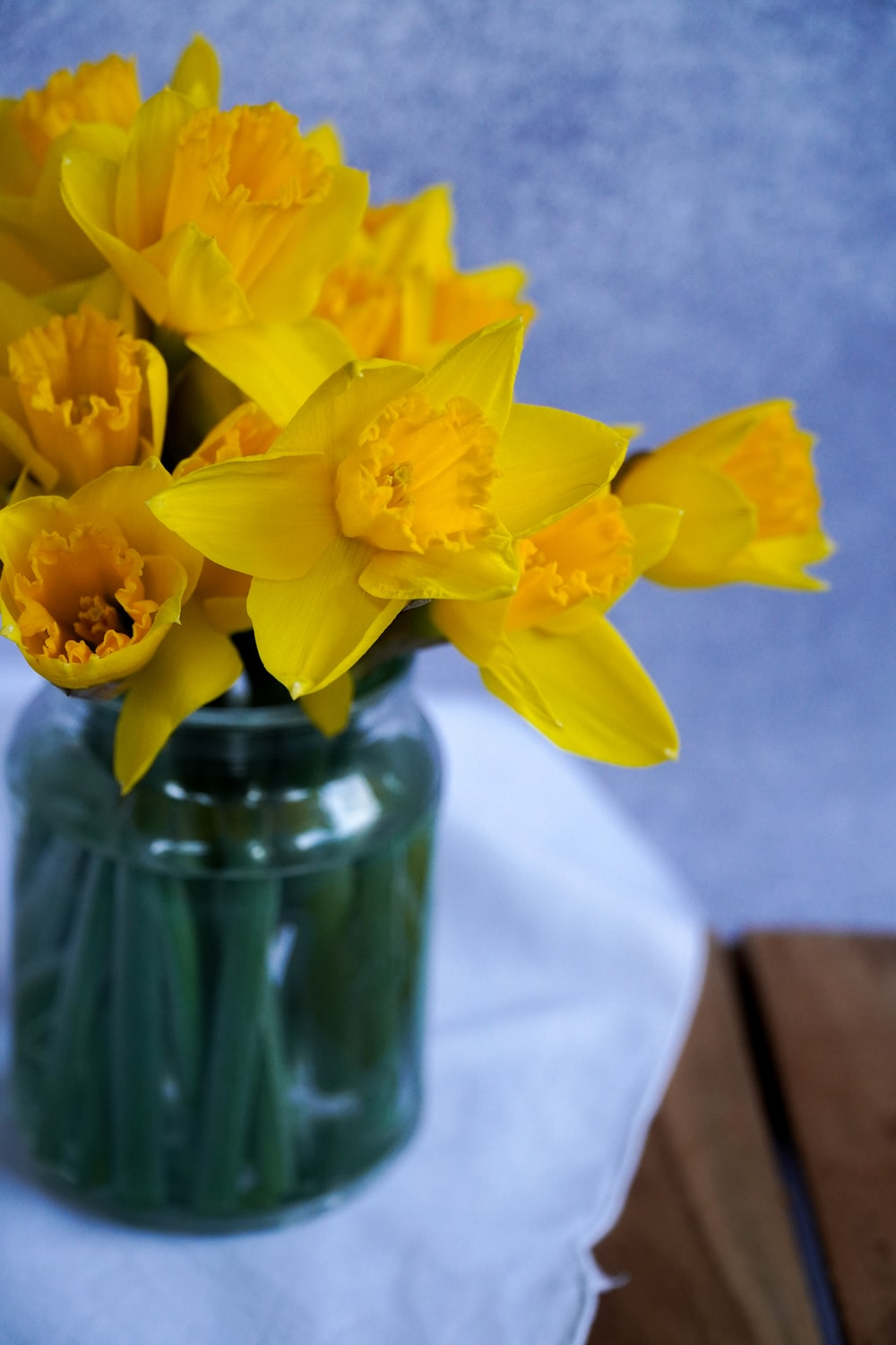 yellow flowers in green glass vase