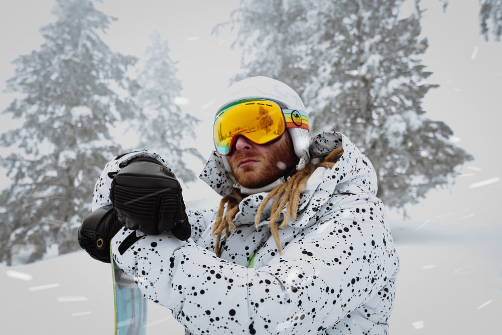 woman in white and black snow goggles and white helmet