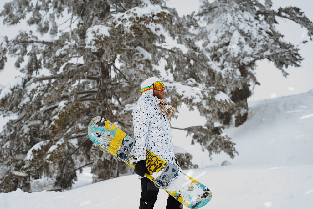 person in white and blue jacket and black pants riding on snowboard during daytime