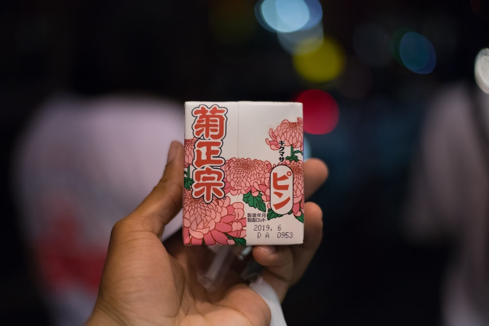 person holding white and red strawberry card