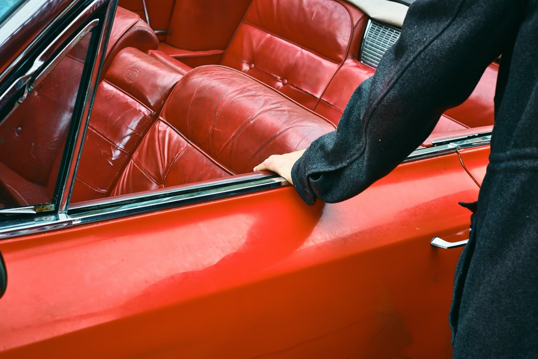 Person In Black Pants Sitting On Red Leather Couch - unsplash