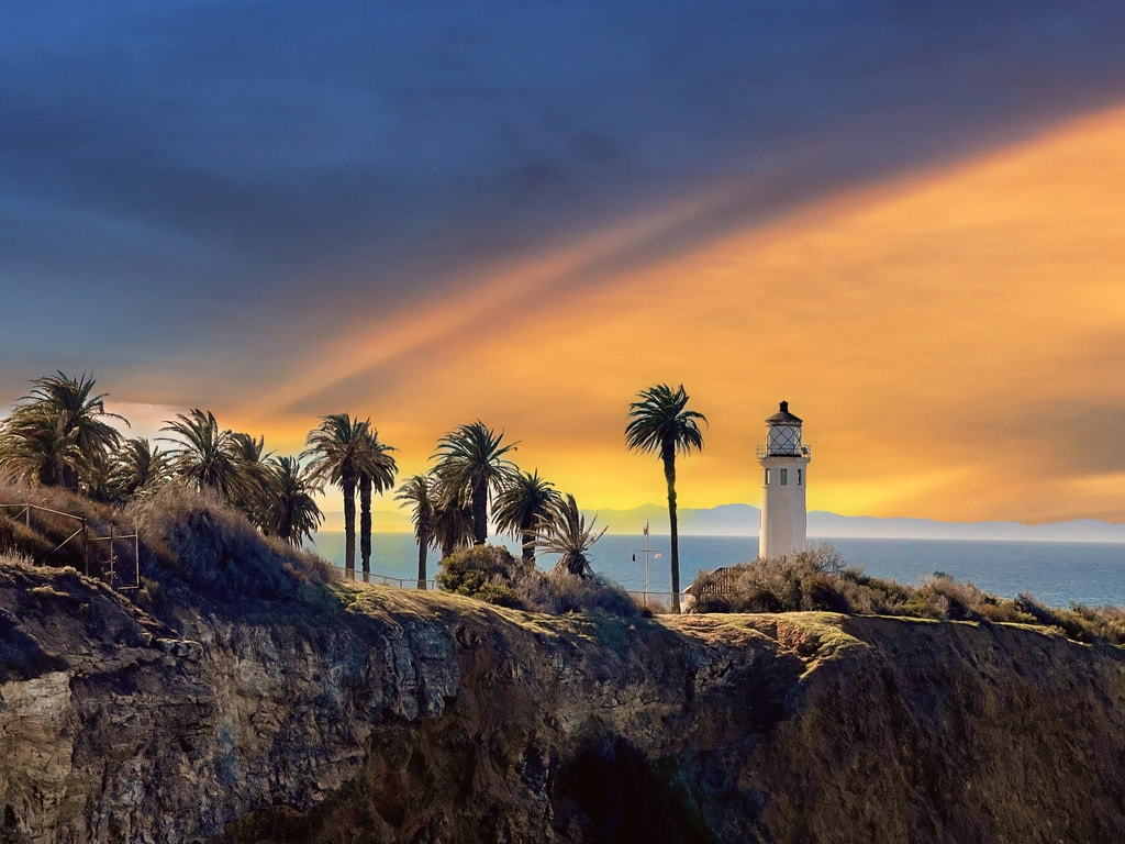 white lighthouse near palm trees during sunset