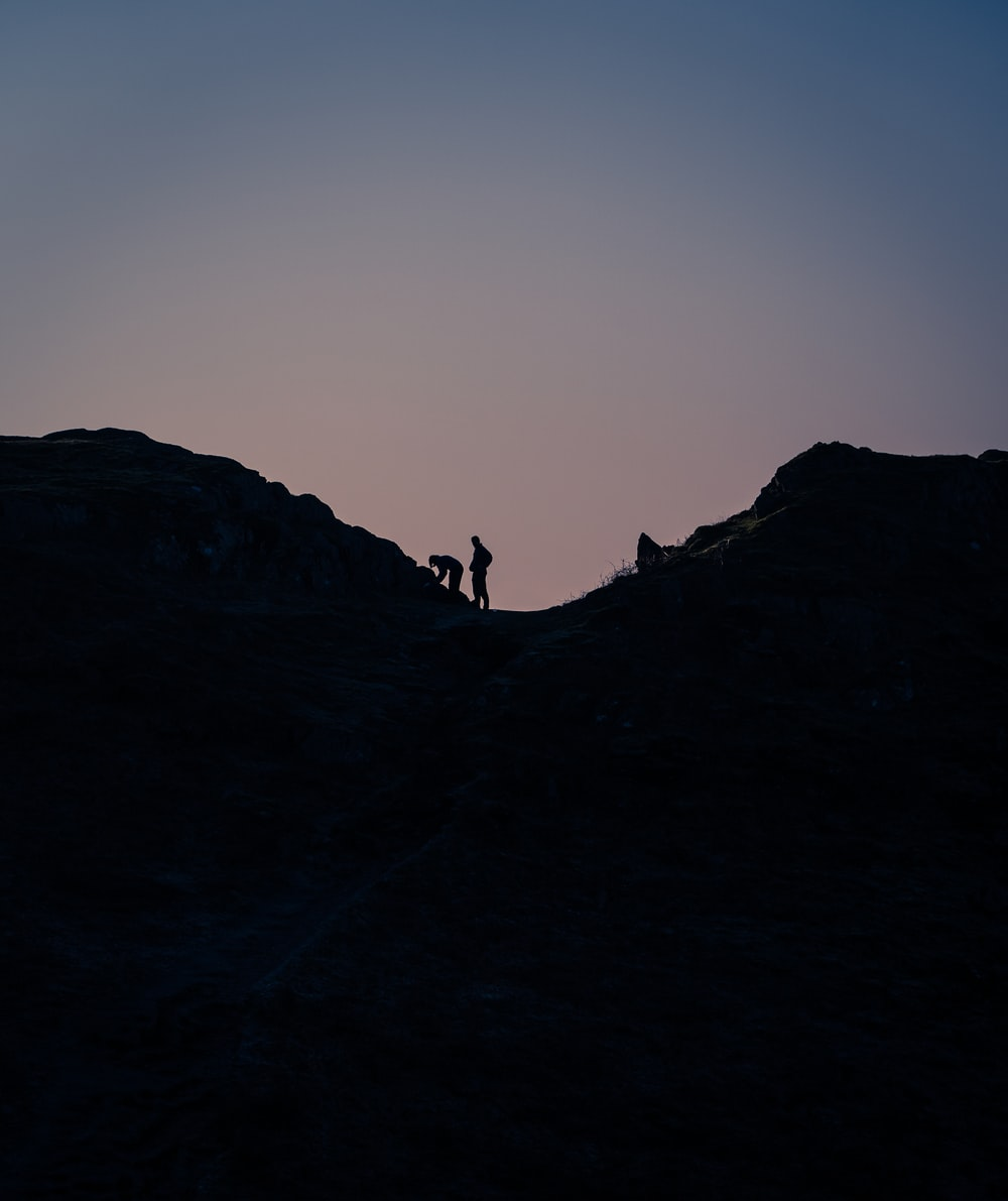 silhouette of 2 people on top of mountain