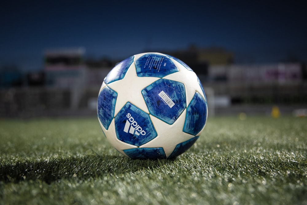 white and blue soccer ball on green grass field