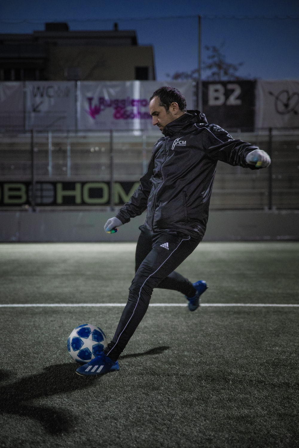 man in black leather jacket and black pants playing soccer