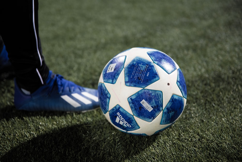blue and white soccer ball on green grass field
