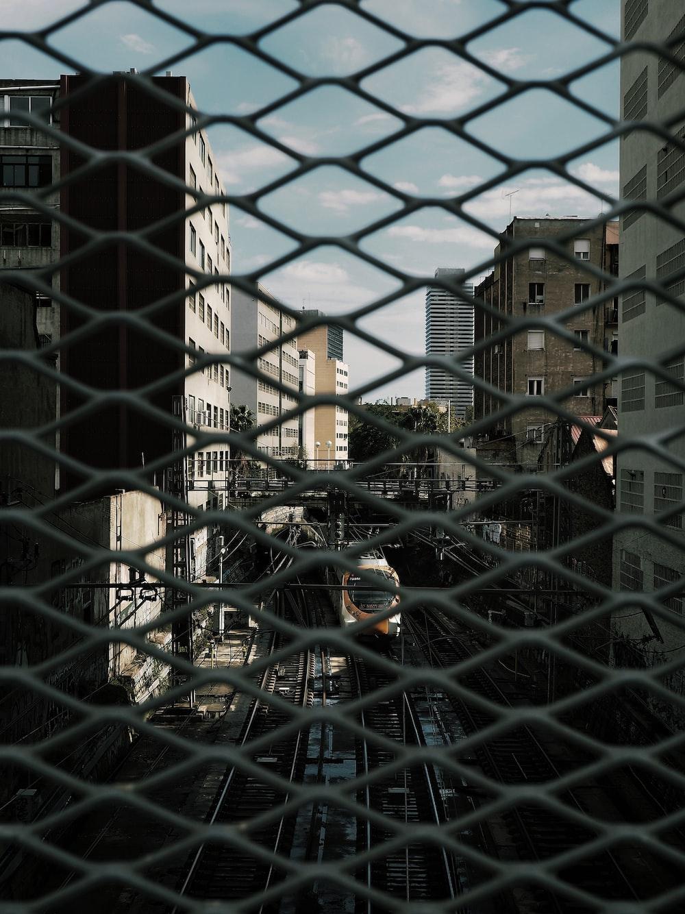 black metal mesh fence near brown concrete building during daytime