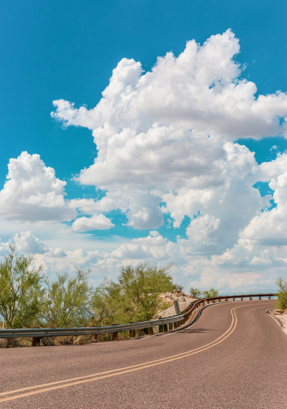 gray concrete road under blue sky and white clouds during daytime