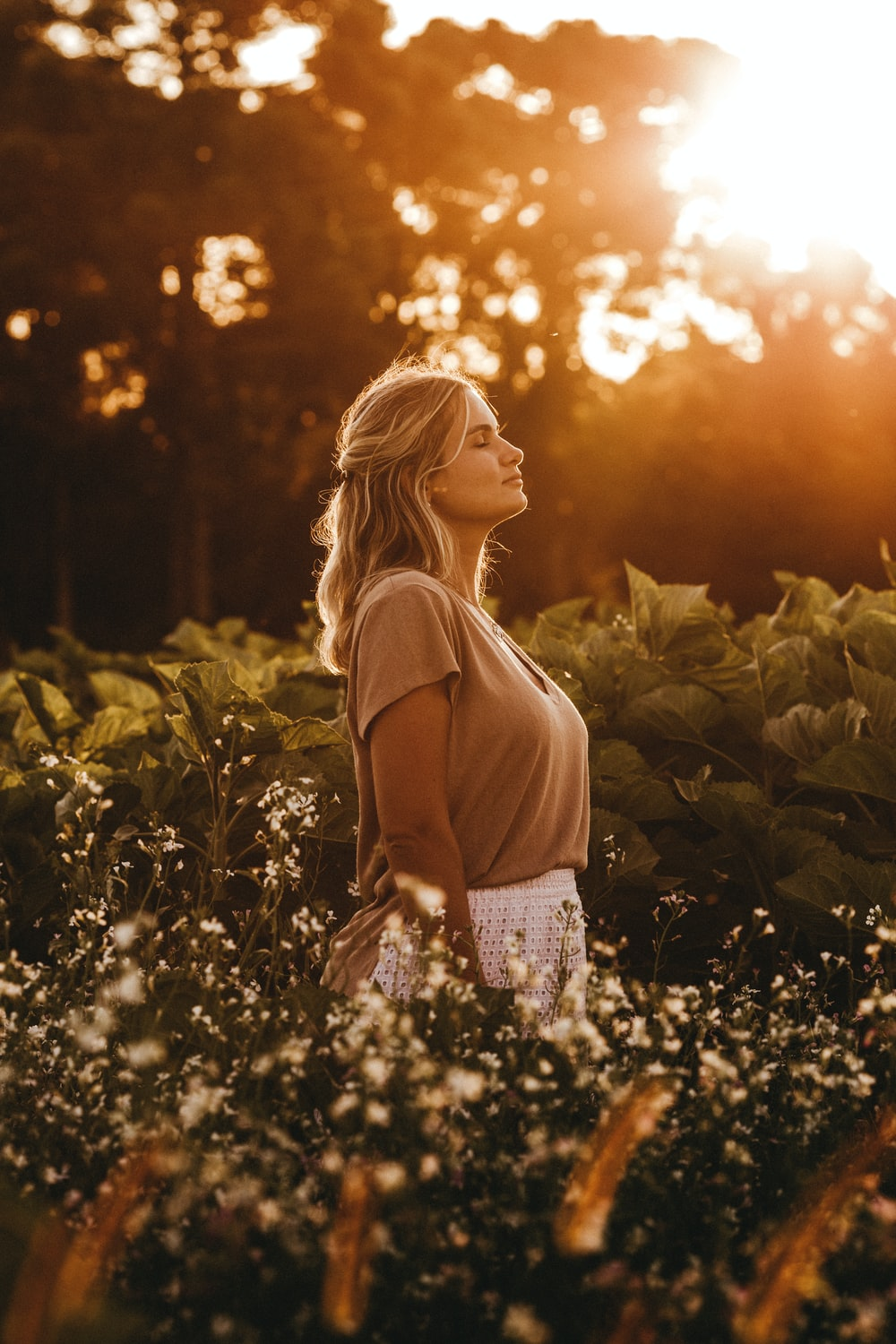 woman in brown tank top standing on green grass field during sunset