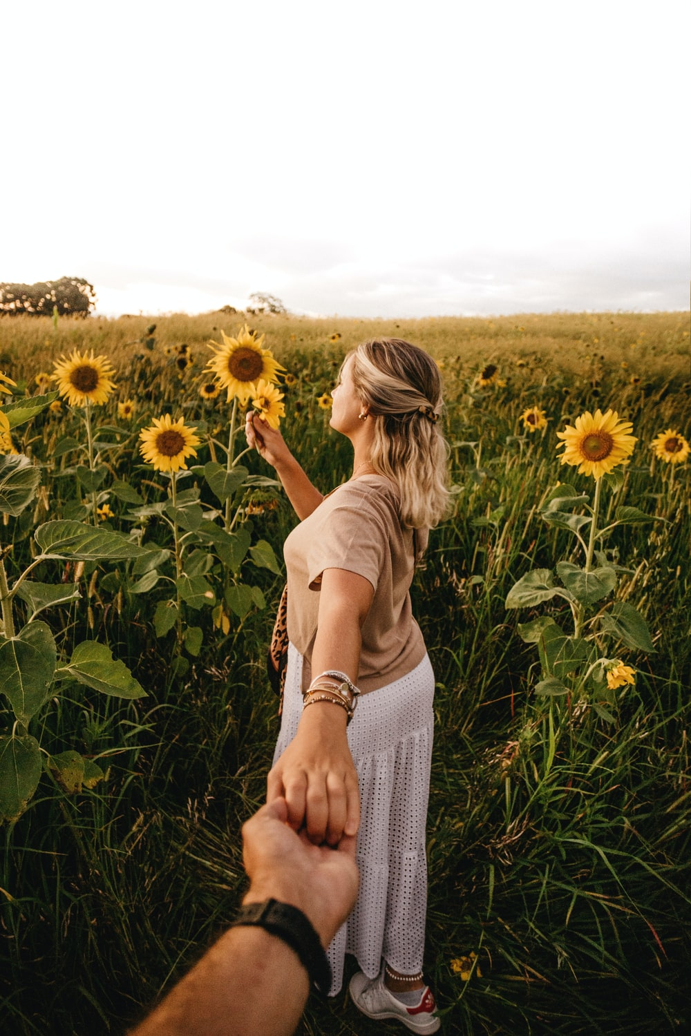 woman in white tank top standing on sunflower field during daytime
