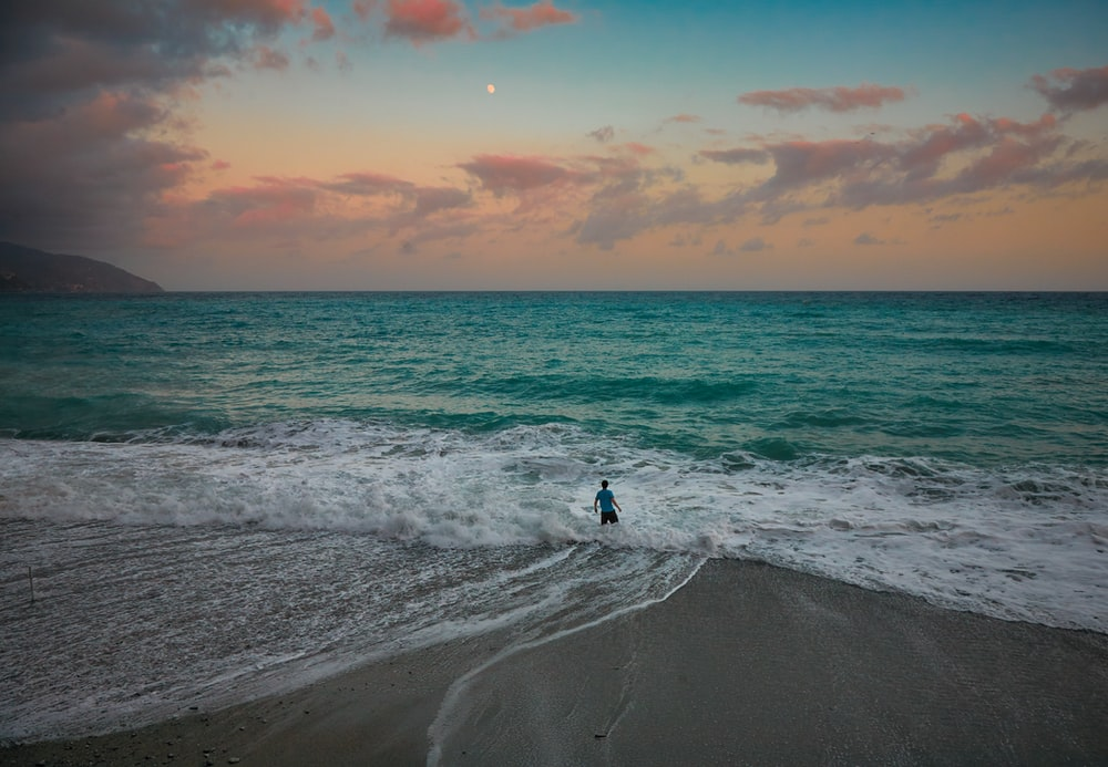 person in black shirt and pants standing on seashore during sunset