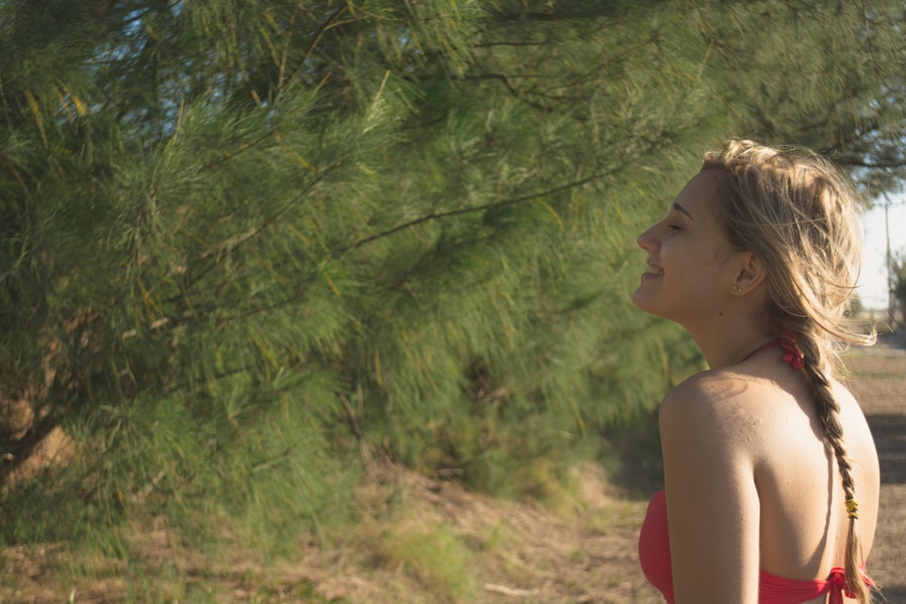 woman in red tank top standing near green trees during daytime