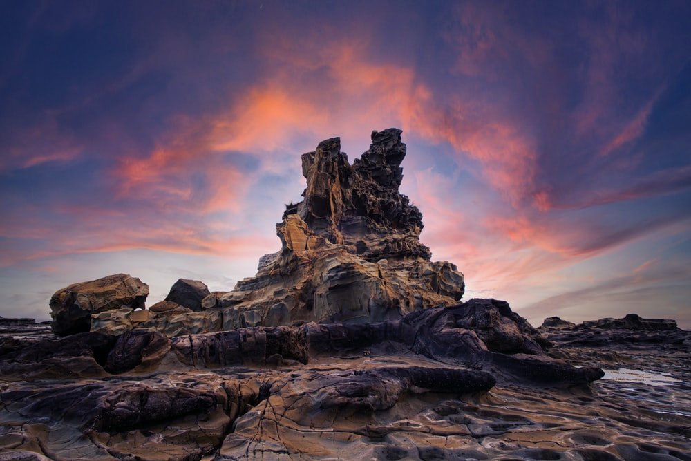 brown rock formation under orange and blue sky