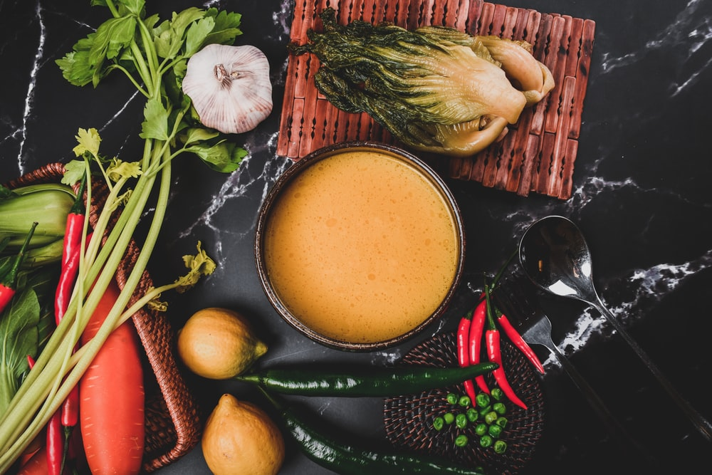 black ceramic bowl with soup beside red chili and garlic