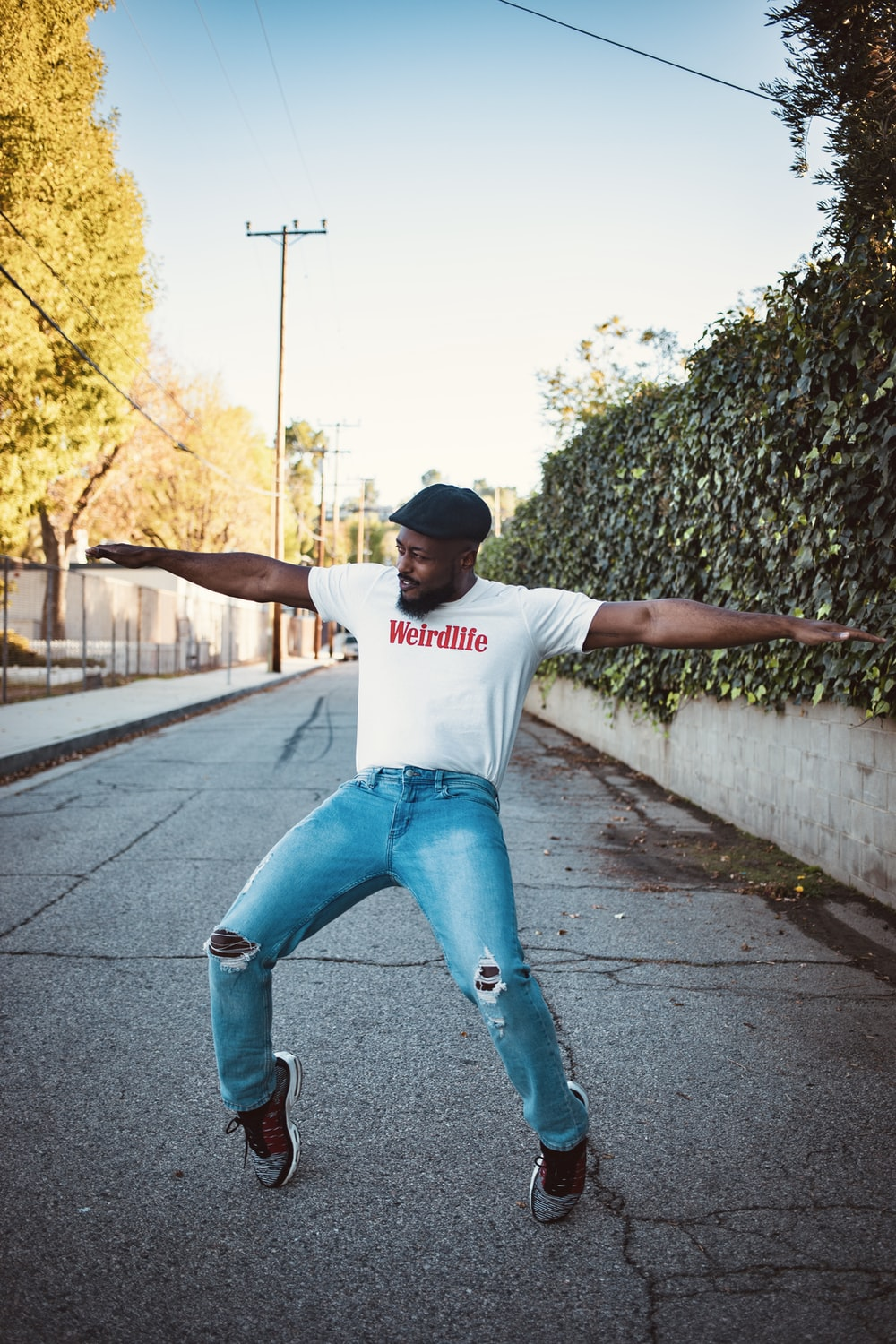 woman in white crew neck t-shirt and blue denim jeans jumping on gray concrete road