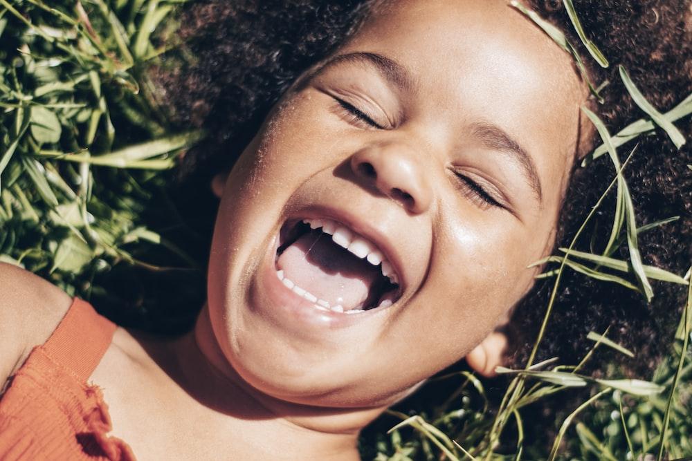 smiling girl lying on green grass