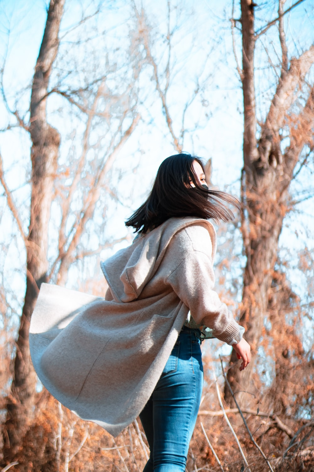 woman in brown long sleeve shirt and blue denim jeans standing near brown trees during daytime