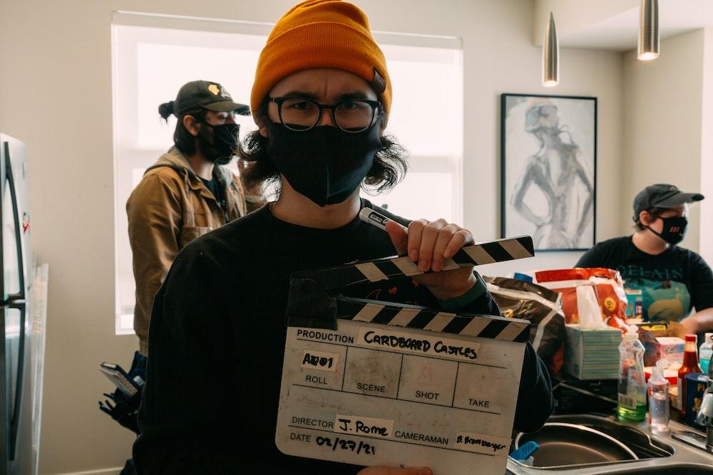 man in black mask holding white printer paper