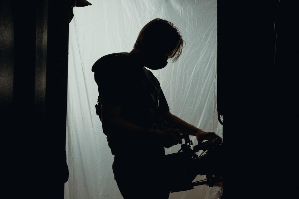 man in black t-shirt standing near white curtain