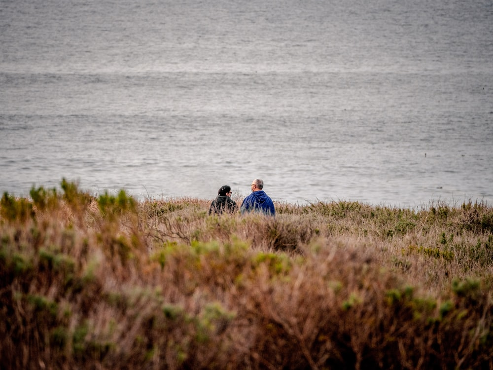 man and woman sitting on grass field near body of water during daytime