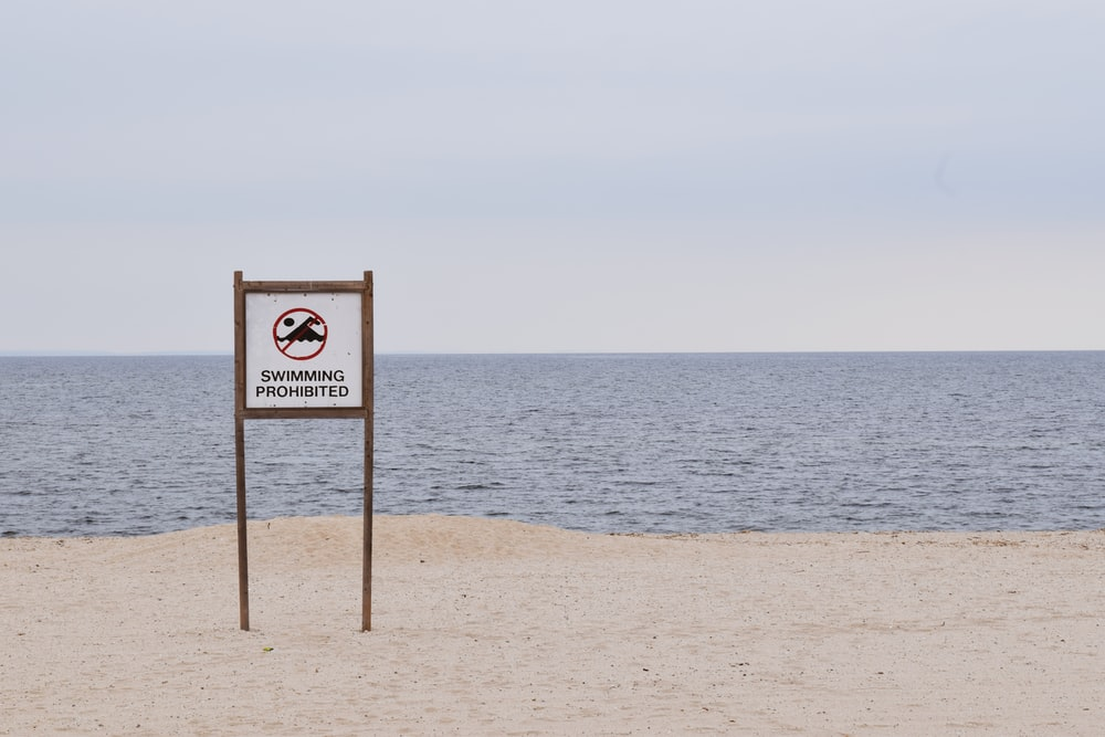 brown and white beach signage on beach during daytime