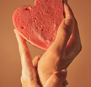person holding pink heart shaped cake