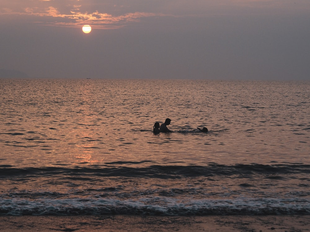 silhouette of 2 people on beach during sunset