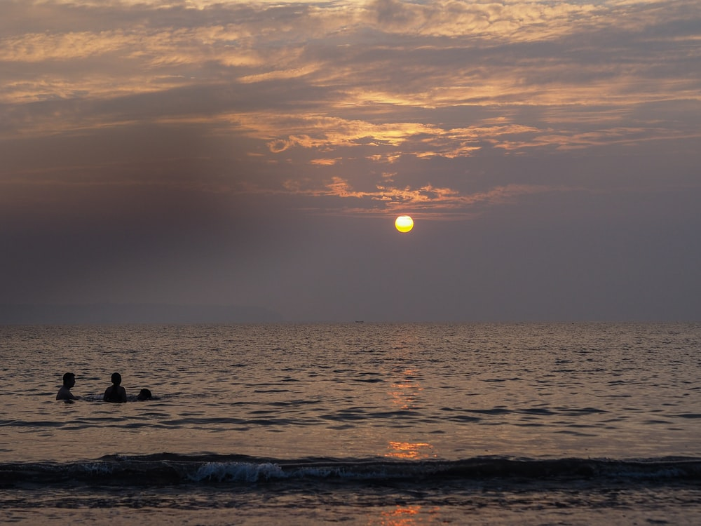 silhouette of 2 people on sea during sunset