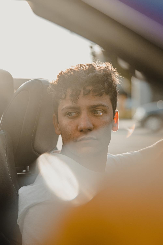man in white dress shirt sitting on car seat