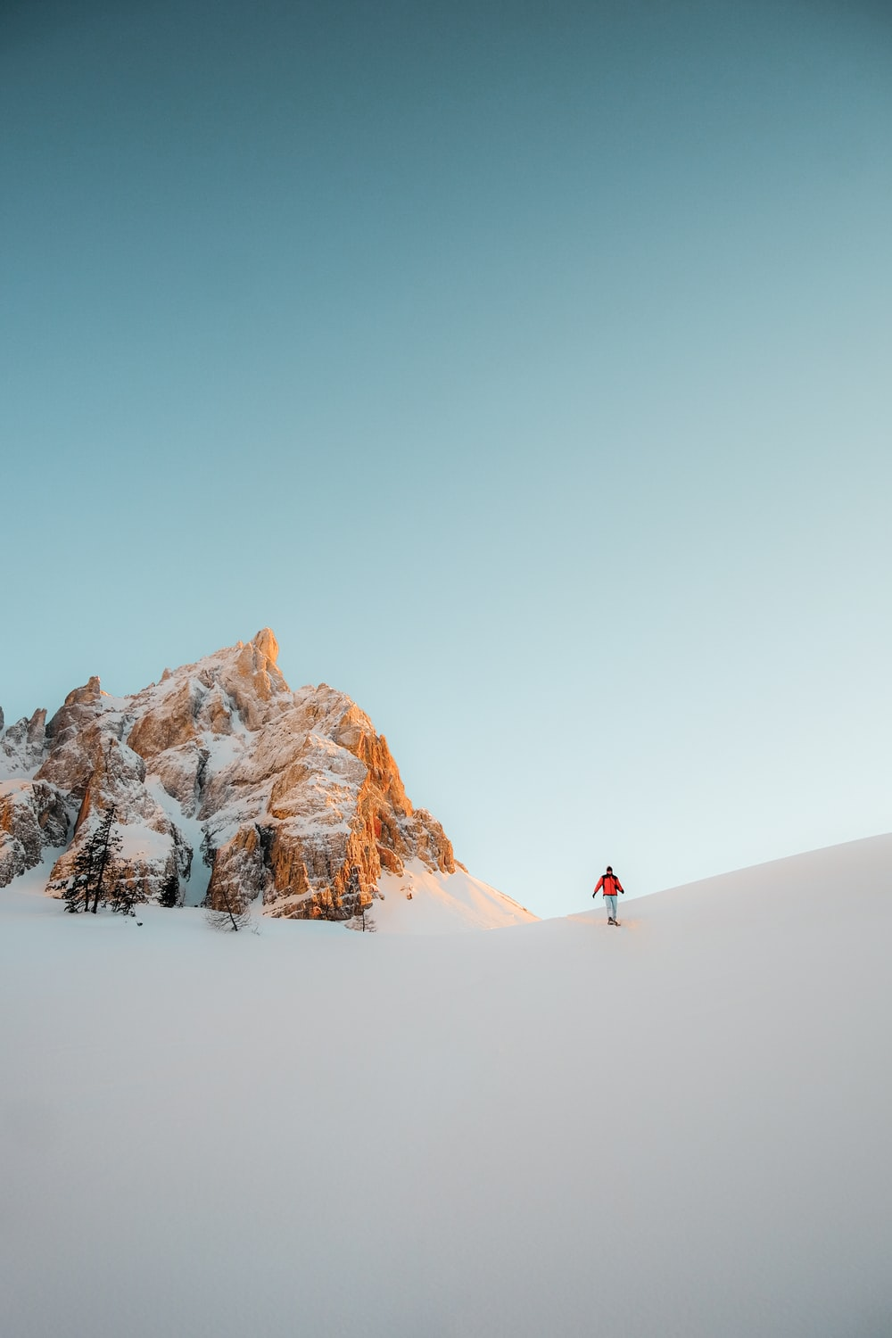 person in red jacket walking on snow covered ground during daytime