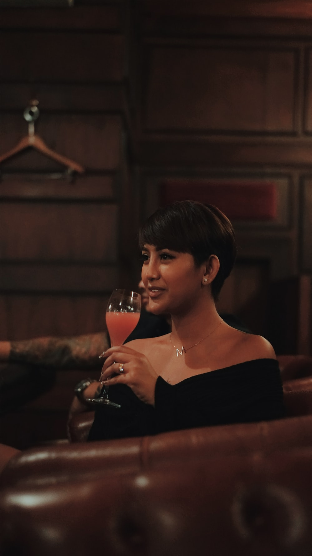 woman in black off shoulder dress holding wine glass