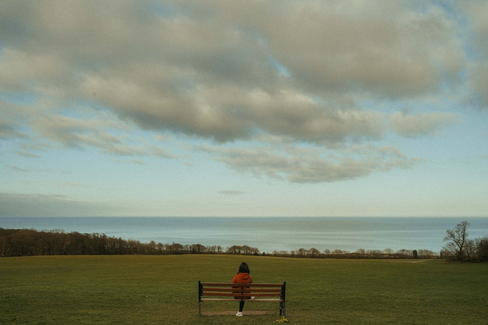 person sitting on bench on green grass field under white clouds during daytime