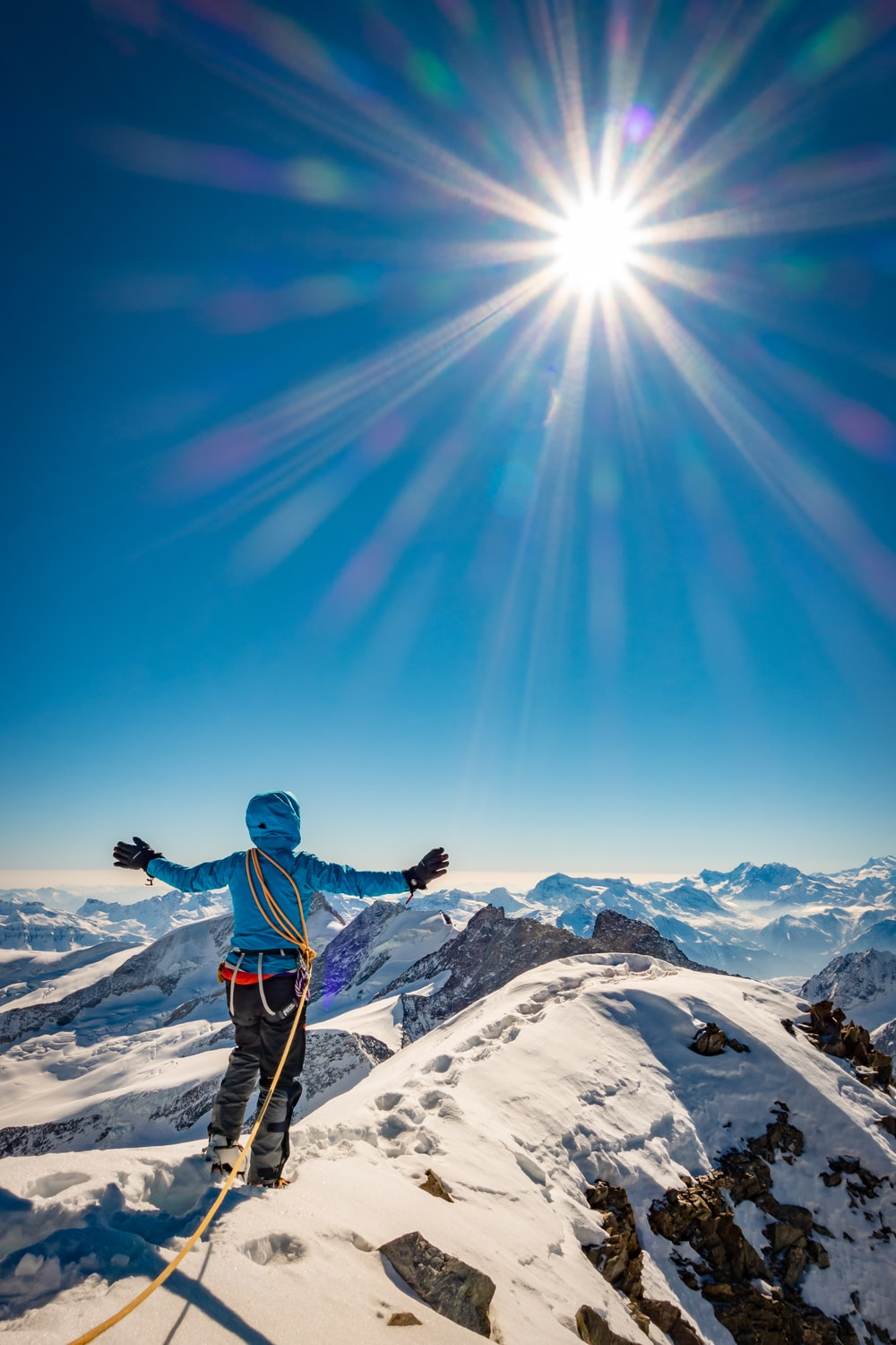 man in blue jacket and black pants standing on snow covered mountain under blue sky during